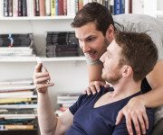 gay-men-partner-using-mobile-phone-together-against-bookshelf-at-home-2