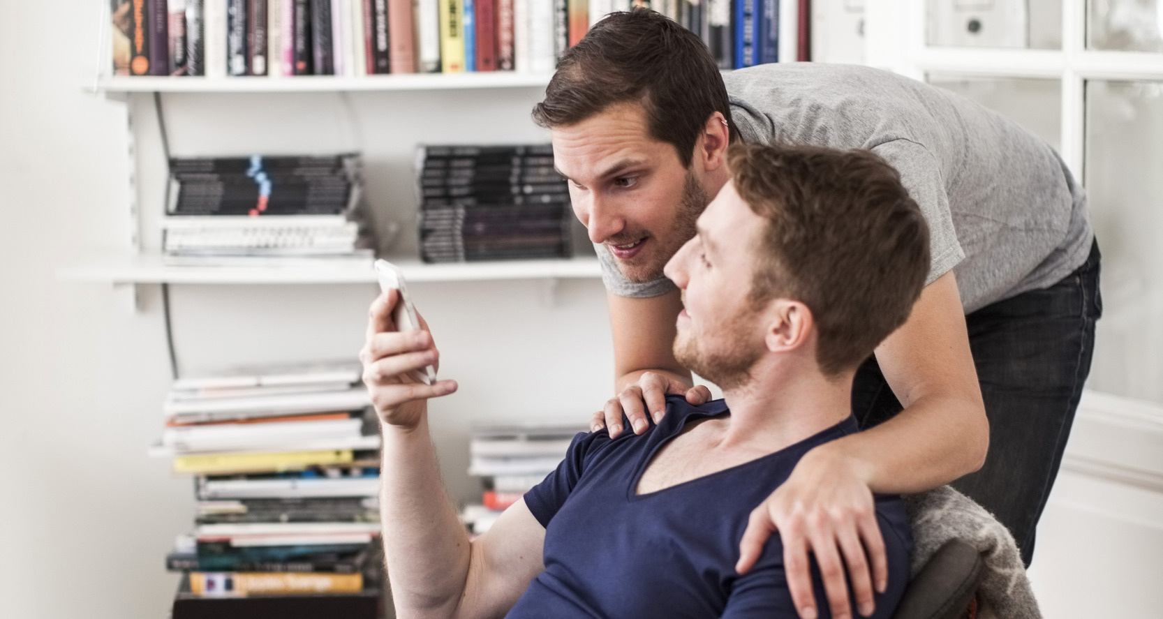 gay-men-partner-using-mobile-phone-together-against-bookshelf-at-home-2